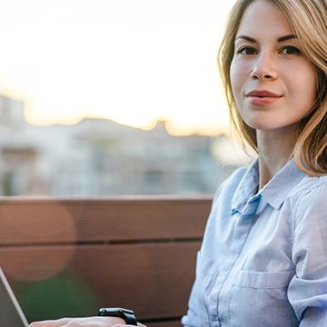 Girl on her laptop before the view of a beautiful landscape